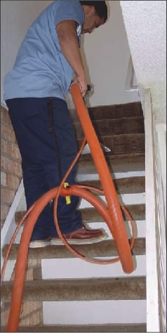 Another View of a Carpet Cleaner has a Stair Climber Attached to Him as He Cleans the Stairs