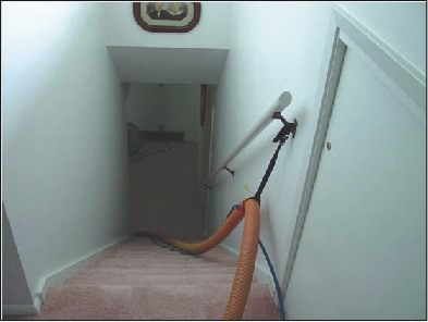 Another View of a Carpet Cleaning Stair Climber Strap Attached to a Hand Rail, Holding a Vac Hose