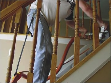 Carpet Cleaner has a Stair Climber Attached to Him as He Cleans the Stairs