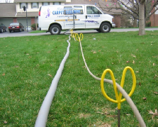 A Group of Yardsticks Holding a Carpet Cleaning Solution Hose Across a Lawn